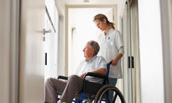Nurse with patient on wheel chair at hospital corr